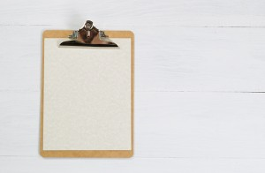 Blank clipboard with paper on white desktop.